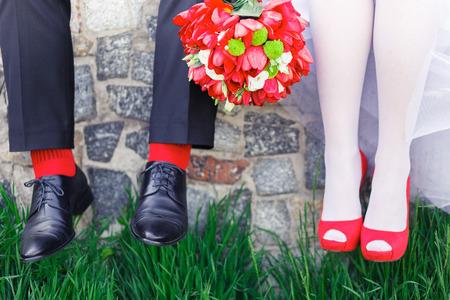 chaussures de mariage des femmes rouges sur l'herbe verte dans le style