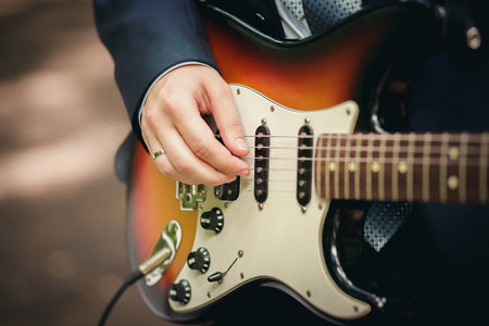 Young beautiful wedding couple electric guitar in the park photo