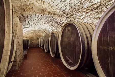 bebidas alcohÓlicas: enormes barriles de vino en una antigua bodega Editorial
