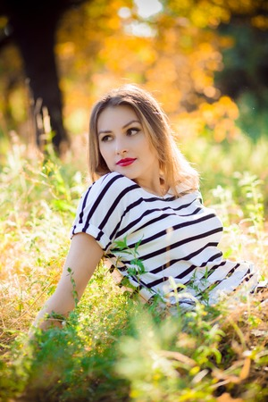 free image: woman sitting on yellow grass in the park