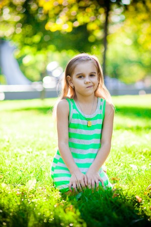 chagrin: displeased little girl on the green grass