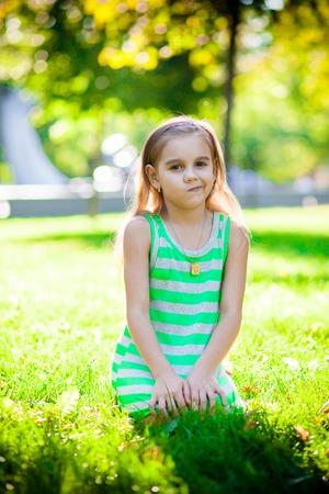 doleful: displeased little girl on the green grass