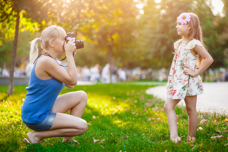 Woman photographing child in the park