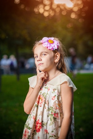 lost in thought: little girl lost in thought in park