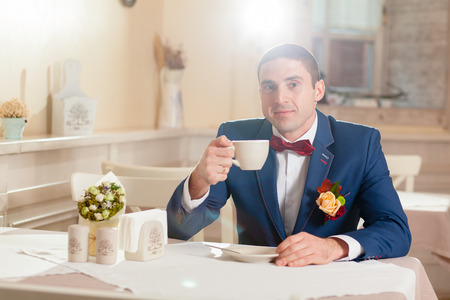 red tie: man with cup in a restaurant red tie Stock Photo