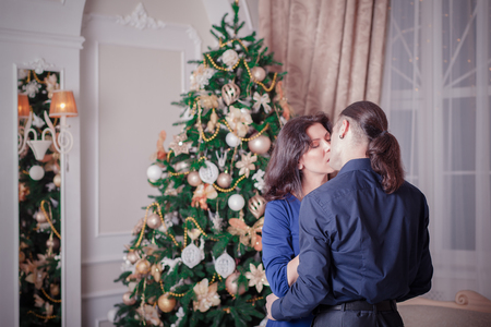 an adult person: young couple near a Christmas tree man woman Stock Photo
