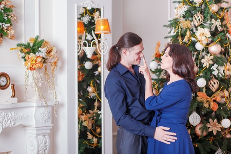adult couple: young couple near a Christmas tree man woman Stock Photo