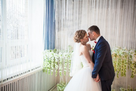 couple nature: wedding studio window light kiss