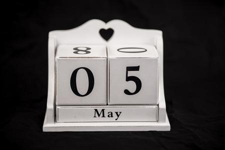 five month old: Calendar cubes black background seasons Stock Photo