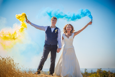 The bride and groom with smoke bombs on the meadow summer