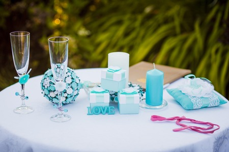wedding night: Wedding. Night. Candles. Composition. On a wooden table from serving dishes and glasses, decorated with candles and a vase with a bouquet of the bride on a white background of the texture