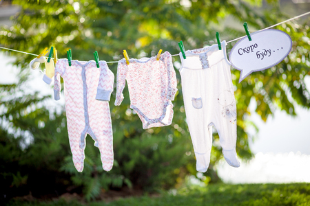 Childrens clothes on a rope in the park, expectations of birth concept