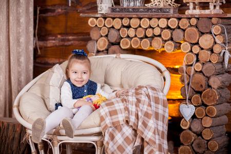 Little girl sitting in rocking chair near fireplace alone