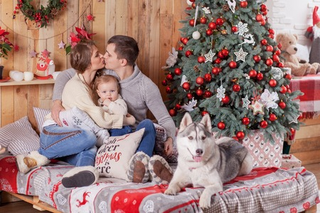 Happy family and a dog Siberian Husky near the fireplace around the Christmas tree Stock Photo