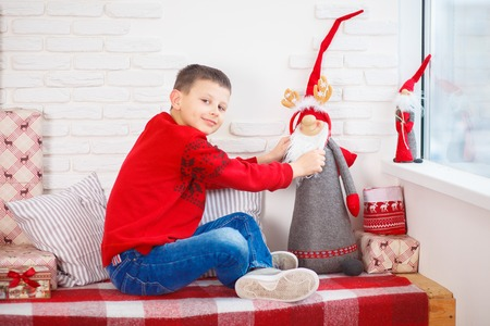 boy in a red sweater christmas tree new year alone
