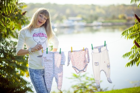 Childs clothes with teddy bear on clothesline on white Stock Photo