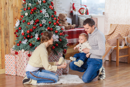 Baby boy on wooden horse swing near christmas decorated tree with parents