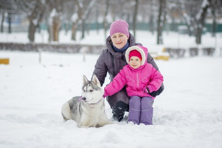 Happy young mother with daughter in the winter park with huskies dog