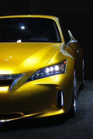 This is a yellow sports car against a dark background and with reflection. Editorial