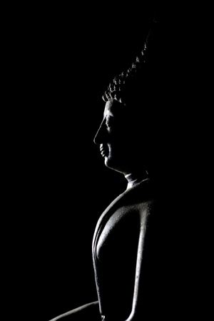 silently: Light of Buddha image in the dark background.