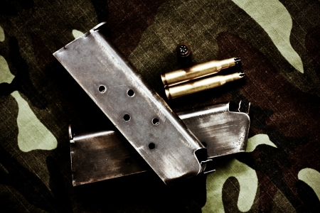bullets and magazine on texture of soldier cloth background photo