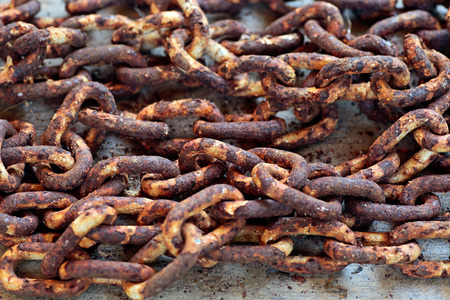 rusty chain on a wooden plank closeup photo