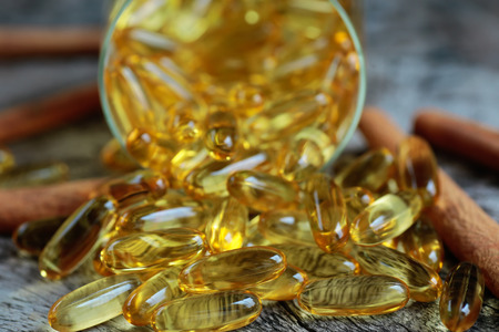 Cod liver oil omega 3 gel capsules isolated on wooden background photo