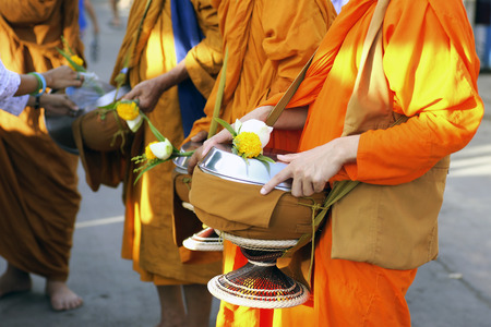 alms: Tourists and locals give alms food to monks during the morning