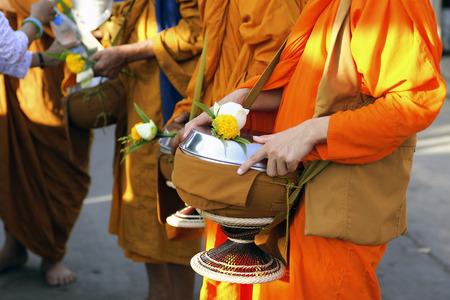 limosna: Turistas y locales dan comida limosna a los monjes durante la mañana Foto de archivo
