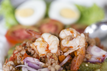 chopped raw vegetables in a frying pan with grilled shrimp Archivio Fotografico
