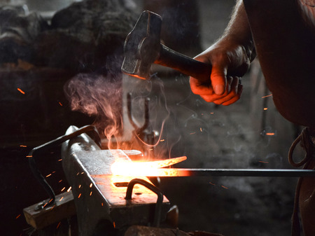 Traditional blacksmith working a piece of iron hot from the furnace.