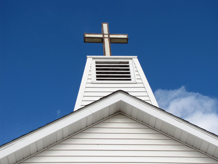 The white steeple of a country church against a blue sky. Banco de Imagens