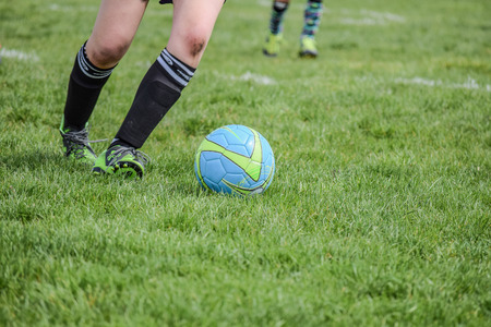 Soccer player dribbling a ball down the field. Imagens