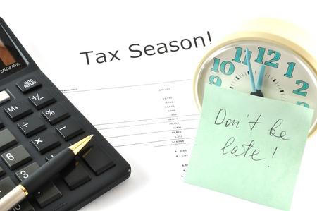 llegar tarde: Imagen conceptual con calculadora y reloj. Temporada de impuestos! No llegar tarde!