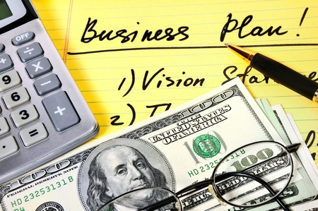 money packs: Business plan with  money, calculator and pen.