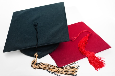 alumna: Black and red graduation caps with tassels on the white background.