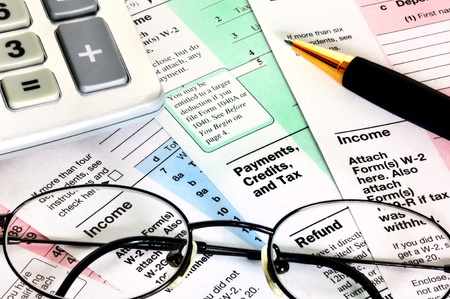 consequence: Business concept. Financial papers with calculator, glasses and pen.