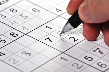 sudoku: Close-up a pencil in hand and logic puzzle Sudoku. Stock Photo