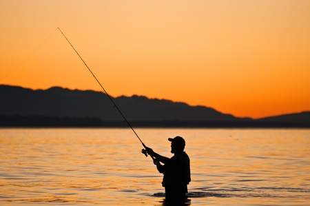Silhouette of a fisherman at sunset.  photo