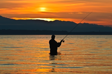 fisher: Silhouette of a fisherman with a fishing pole at sunset.