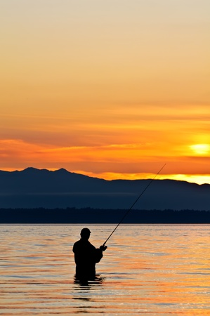 Silhouette of a fisherman with a fishing pole at sunset. photo