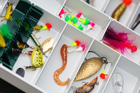 A fisherman tackle box with lures and gear for fishing. photo