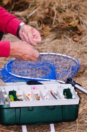 A fisherman on the riverside binds fish hook.