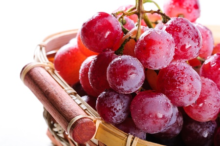Bunch of red grapes in a basket on a white background.