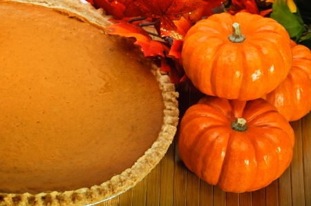 Pumpkin pie in a pie plate with autumn leaves and pumpkins. photo