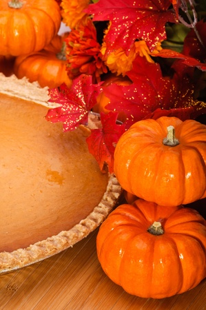 Pumpkin pie in a pie plate with autumn leaves and pumpkins.