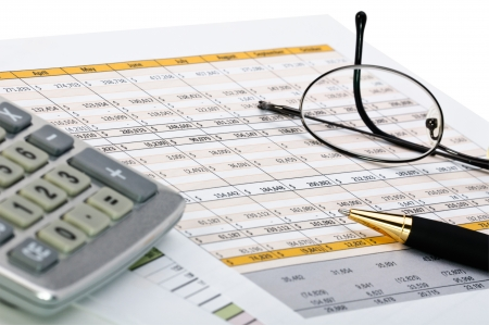 tax return: Financial forms with pen, calculator and glass. Stock Photo