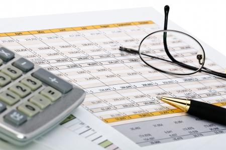 renta: Formas financieras con l�piz, calculadora y el vidrio. Foto de archivo