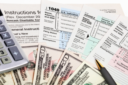 refund: Tax forms 1040 with pen, calculator and money.