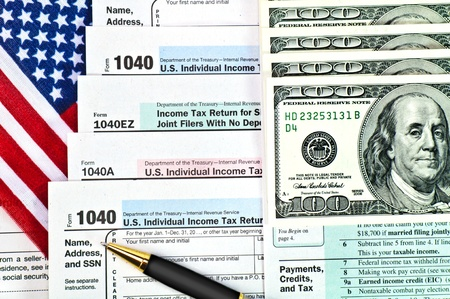tax forms: Tax forms 1040 with U.S. flag, pen and money. Editorial